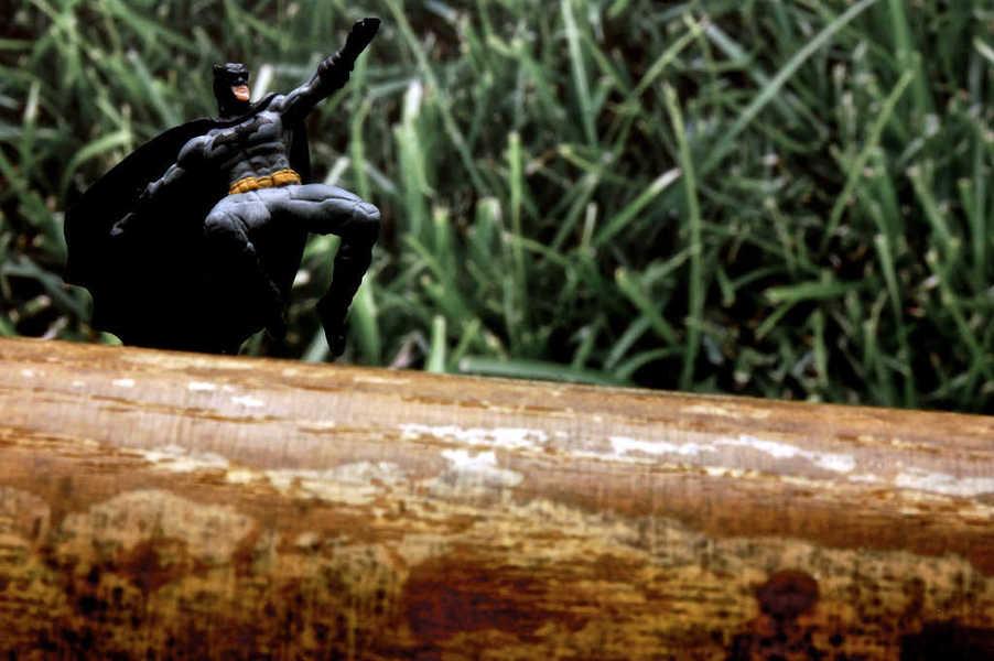 Photo of a tiny Batman leaping over a baseball bat