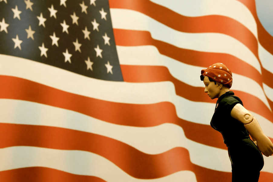 Photo of Rosie the Riveter in front of the US flag